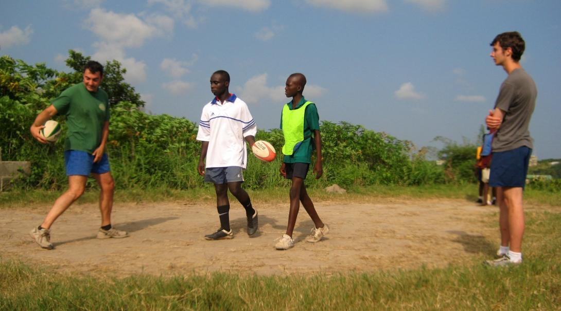 A volunteer teaching rugby in Ghana demonstrates passing techniques to local players